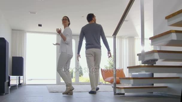 Krásný mladý pár vstoupí do jejich nově zakoupeného domu jsou velmi šťastní. Jejich domovem je světlé, moderní a má od podlahy až ke stropu Windows
