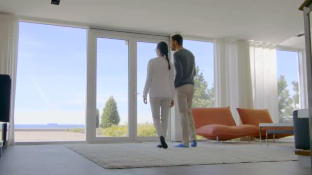 Beautiful Young Couple In Their Newly Purchased House, They Look at the Sea Through Floor to Ceiling Windows. Their Luxury Home is Bright, Modern with Tastefully Made Interior.
