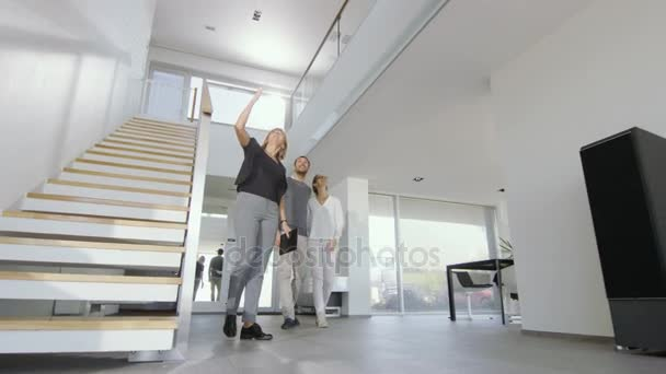 Professional Real Estate Agent Shows Stylish Modern House to a Beautiful Young Couple.
