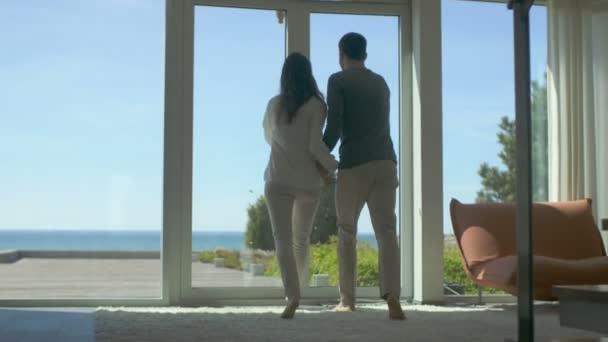 Po Shot balkonové dveře otevírací nádherný pár a chůze na slunné terase s výhledem na moře. Obloha je Cloudless a lidé jsou Happy
