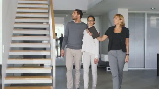 Professional Real Estate Agent zeigt stilvolles modernes Haus eine schöne junge Ehepaar, das auf dem Markt zum Kauf / Vermietung Home neu sind. Haus ist Modern, stilvoll und hell