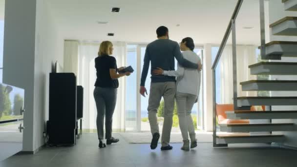 Professional Real Estate Agent zeigt stilvolles modernes Haus eine schöne junge Ehepaar, das auf dem Markt zum Kauf / Vermietung Home neu sind. Haus ist vom Boden bis zur Decke reichenden Fenster und Blick aufs Meer