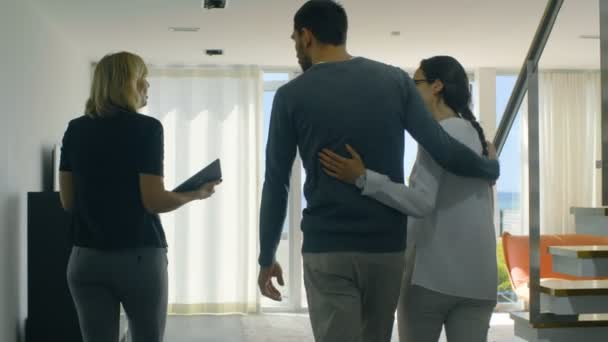 Profesionální realitní makléř ukazuje stylový moderní dům krásný mladý pár, kteří jsou na trhu pro nákup / pronájem nových domů. Dům má patro francouzskými okny a výhledem na moře.