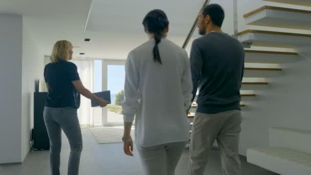 Profesionální realitní makléř vítá krásná mladá dvojice do prostorných a moderních domů. S podlahou francouzskými okny a výhledem na moře