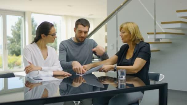 Sedí u stolu v obývacím pokoji realitní Agent a krásná mladá dvojice značek dokumenty a šťastně obejmout. Dům je slunečné a jasné