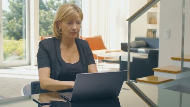 Krásná starší žena používá notebook, zatímco sedí na pohovce v obývacím pokoji své slunné. Dům má patro okna s výhledem na moře. Počasí je Slunečné