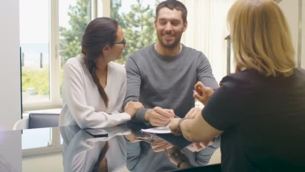 Sedí u stolu v životních krásný mladý pár uzavřely smlouvu a kupuje dům, realitní Agent dává jim klíče od domu. Novomanželé, obejmout šťastně. Domov je slunečné a jasné