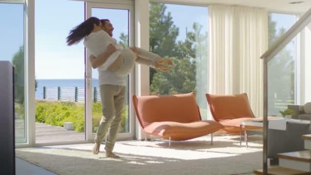 V slunný obývací pokoj pohledný mladý muž zvedne svou krásnou přítelkyní a Spin objetí. Oni jsou Happy a dům je Sunny s výhledem na moře.
