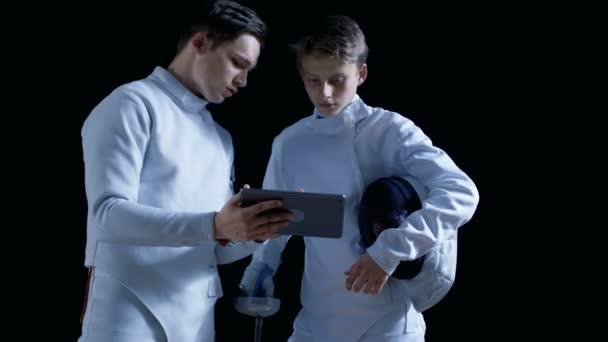 Dva mladí šermíři plně vybavenou pomocí tabletového počítače Další informace o strategii, útoku a obrany v šermu. Shot izolované na černém pozadí.