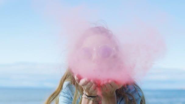 Krásná mladá dívka s hnědými vlasy a stylové sluneční brýle fouká Holi barevný prášek z rukou a smích. Jasné modré oblohy za ní