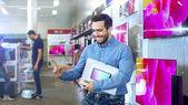 Fényképek Fiatalember, elektronikai boltban vásárolt legújabb modell, a lap