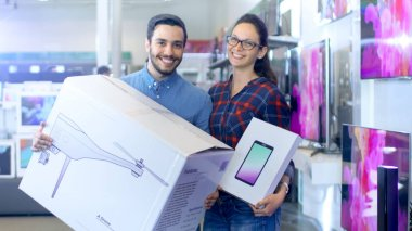In the Electronics Store Happy Young Couple Poses with Newly Pur