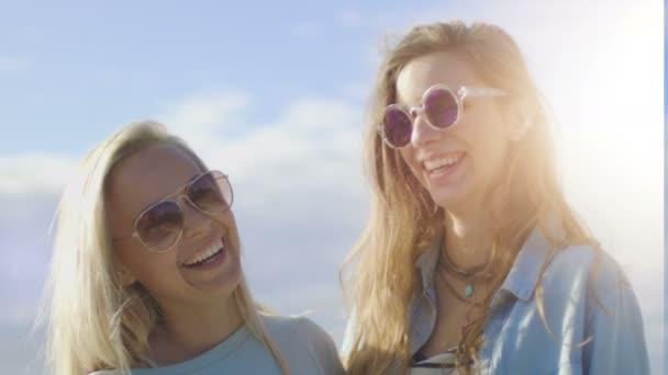 Portrét Shot dvě krásné dívky nosí sluneční brýle, objímání, pózování a usmíval se na kameru. Mají spoustu letní zábavy. V pozadí je vidět jasné modré nebe