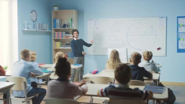 Tehetséges tanár elmagyarázza a leckét egy osztályteremnek, ami tele van ragyogó, változatos gyerekekkel. Az általános iskolában az intelligens többnemzetiségű tanulás geometriája és fizikája, fiú felemelő kéz egy választ