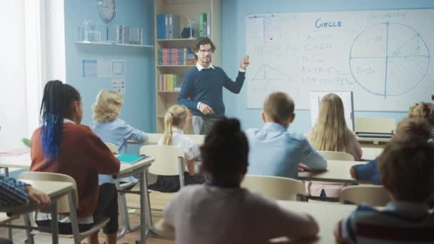 A gondoskodó tanár elmagyarázza a leckét egy sokszínű gyerekekkel teli osztályteremnek. In School with Group of Smart Multiethnic Kids Learning Science, Az egész osztályteremben felemeli a kezét ismerő választ. Lassú mozgás