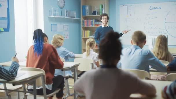 A gondoskodó tanár elmagyarázza a leckét egy osztályteremnek, ami tele van ragyogó, változatos gyerekekkel. Az Általános Iskolában az Okos Többnemzetiségű Gyerekek Tanulástudományi Csoportjával. Lassú mozgás mozgó kamera