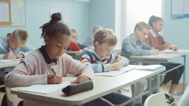 Základní třída různorodých bystrých dětí Pozorně naslouchají svému učiteli, který dává lekci. Brilantní mladé děti ve škole Psaní ve cvičebních sešitech, Absolvování testu. Postranní pohled pohybující se fotoaparát