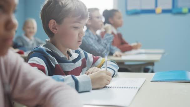 In der Grundschulklasse: Porträt eines brillanten kaukasischen Jungen, der im Aufgabenheft schreibt, Test macht und Prüfungen schreibt. Vielfältige Gruppe aufgeweckter Kinder, die fleißig arbeiten und lernen