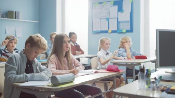 A gyermekek általános osztályterme Figyelmesen hallgatja a tanárukat, amint leckét ad. Mindenki felemeli a kezét, tudván a helyes választ. Fiatal gyerekek az iskolai tanulásban Tudomány és kreatív gondolkodás