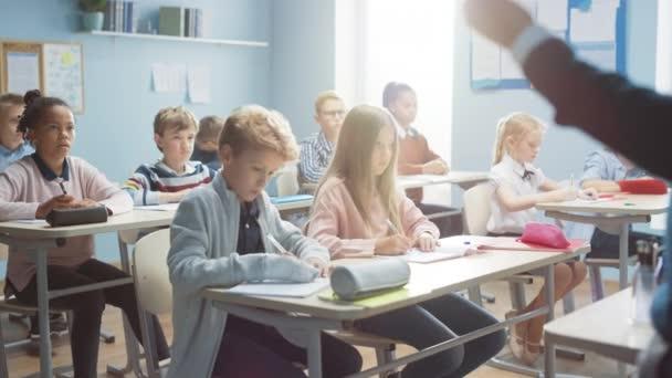 A Sokszínű Gyermekek Általános Osztálya Hallgatja a Tanárt, amint leckét ad. Mindenki felemeli a kezét, tudván a helyes választ. Fiatal gyerekek az iskolai tanulás tudománya, kreatív gondolkodás