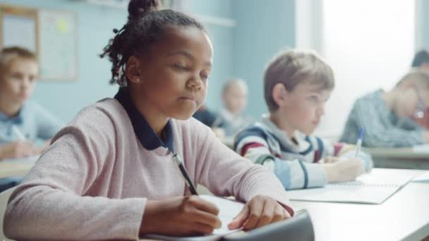Általános iskolai osztály: Portré egy briliáns fekete lány fogszabályzóval írja a gyakorlat notebook, Smiles. Junior tanterem a változatos gyermekcsoport tanulási új dolgokat