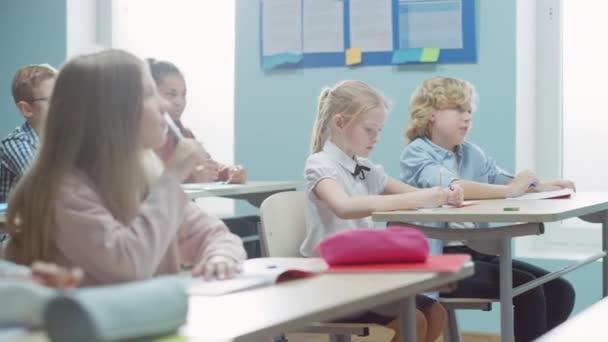 A sokszínű gyerekek általános osztályterme Figyelmesen hallgatva a tanárukat, aki leckét ad. Brilliáns fiatal gyerekek tanulnak az iskolában, írnak a gyakorló jegyzetfüzetekbe, teszteket csinálnak. Mozgó kamera