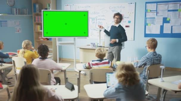 Az általános iskolai tanteremben: A tanár horizontális zöld makett képernyőt használ interaktív digitális táblára, hogy elmagyarázza a leckét az iskolások diverzifikált csoportjának. Multi Ethnic Kids Learning Science