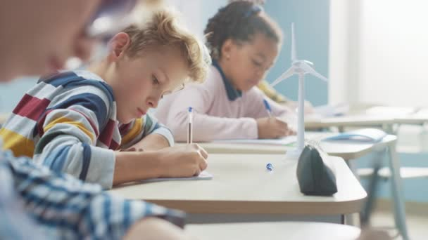 In Elementary School Classroom Brilliant Caucasian Boy Writes in Exercise Notebook, Taking Test and Writing Exam. Junior Classroom with Group of Children Working Diligently and Learning New Stuff