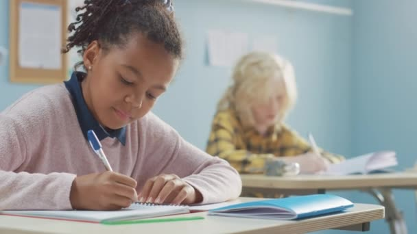 V základní škole učebna Brilantní černá dívka píše v zápisníku cvičení, Dělat test a psaní zkoušky. Třída mladých se skupinou bystrých dětí pilně pracujících a učení se novým věcem