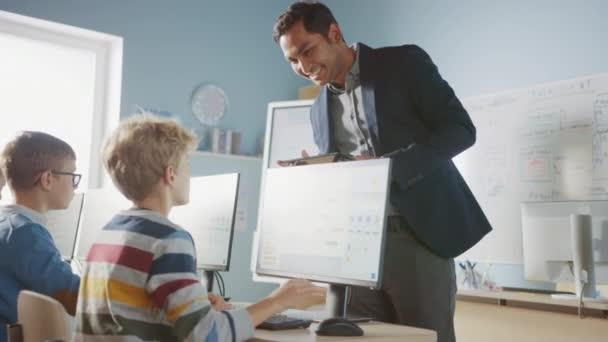 Informatikunterricht in der Grundschule: Lehrer benutzt Tablet-Computer, erklärt verschiedenen intelligenten Kindern den Unterricht, gibt einem Jungen High Five. Informatikkurs für Kinder