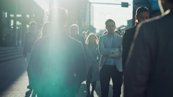 Kancelářští manažeři a obchodní lidé dojíždějí do práce ráno nebo z kanceláře za slunečného dne pěšky. Chodci jsou elegantně oblečeni. Úspěšní lidé vypadají seriózně a soustředěně.