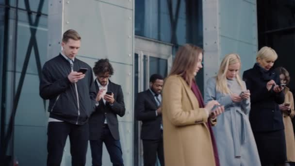 Office Managers and Businessmen are Standing in Front of a Modern Glass Office Building and Use Their Smartphones. People are Dressed Smartly and Look Successful. They are Occupied by Their Devices.