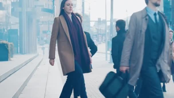 Různí a multikulturní kanceláře manažeři a obchodní lidé dojíždějí do práce ráno nebo z kanceláře za slunečného dne pěšky. Chodci jsou elegantně oblečeni. Dva podnikatelé potřást rukou.
