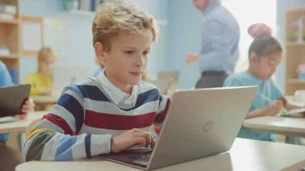 Általános Iskola Számítástechnikai Osztály: Okos fiú Laptop Számítógépet használ, osztálytársai laptopokkal is dolgoznak. A gyermekek modern oktatásban részesülnek a STEM-ben, a játékban és a tanulásban