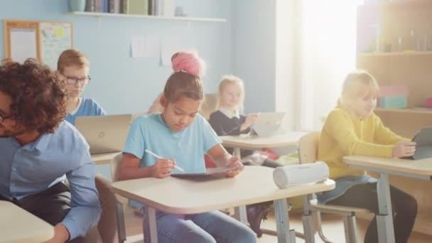 Základní škola počítačové vědy třída: Chytrá dívka používá digitální tablet počítač, Její spolužáci pracují s notebooky, Přátelský učitel procházky kolem třídy pomáhá dětem. Děti získávají moderní vzdělání