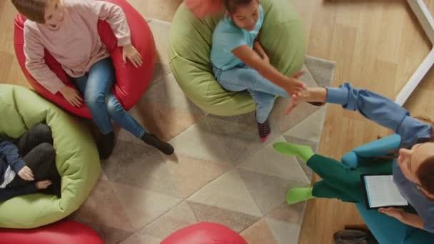 Elementary School Creativity Classroom: Kinder, die auf den Bohnensäcken sitzen, während der Lehrer ihnen den Unterricht erklärt und digitale Tablet-Computer verwendet, spielen, indem sie High Five bestehen. Kamera von oben
