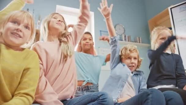 Grundschulkreativitätsklasse: Verschiedene Kinder sitzen auf dem Teppich und heben die Hände mit vorgefertigten Antworten. Lernen in einer modernen Umgebung. Niedrigwinkelkamera