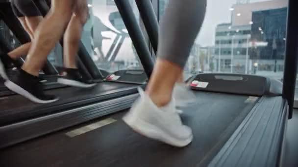 Atlétikai emberek futnak futópadlón, Fitness gyakorlatot végeznek. Erős Női és Férfi Edzés a Modern Tornateremben. Sportemberek Edzése a Fitness Klubban. Alacsony talpú lövés fókuszban a lábak