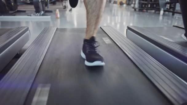 Atlétikai Izomember futás futópad, láb és kardio nap. Erős Ember Képzés Modern Tornateremben. Sportemberek Edzése a Fitness Klubban. Elülső nézet a Low Ground Shot lassú mozgásban. Koncentrálj a lábakra