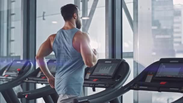 Athletischer Muskelmann, der auf einem Laufband, Bein und Herz-Kreislauf-Tag läuft. Krafttraining im Modern Gym Fitness Club. Rückansicht Slow Motion Kamera Shot