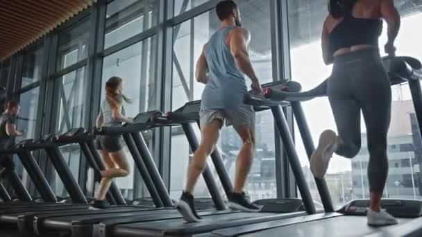 Hat Atlétikai Emberek Futópadlón Futnak, Fitnesz Gyakorlatot végeznek. Atlétikai emberek Aktívan edzenek a modern edzőteremben. Sportemberek Edzése a Fitness Klubban. Alacsony szögű oldalnézet lassú mozgásban