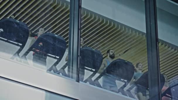 Sportliche Menschen, die auf Laufbändern laufen und Fitnessübungen machen. Fitte und muskulöse Sportler trainieren aktiv in der modernen Turnhalle. Sports People Workout. Niedrigwinkel-Kamera von außerhalb des Gebäudes aufgenommen