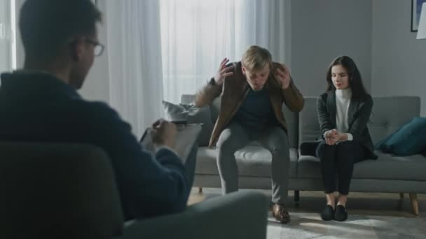 Young Couple on a Counseling Session with Psychotherapist. Back View of Therapist Taking Notes: Angry and Aggressive Husband loses Temper, Starts Screaming, His Suffering Partner Tries to Calm Him