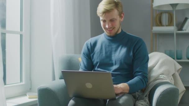 Portrét pohledné blondýny Mladý muž pracující na notebooku, zatímco sedí na židli ve svém útulném obývacím pokoji. Creative Freelancer Relaxes at Home, Surfs Internet, Používá sociální média, a uvolňuje