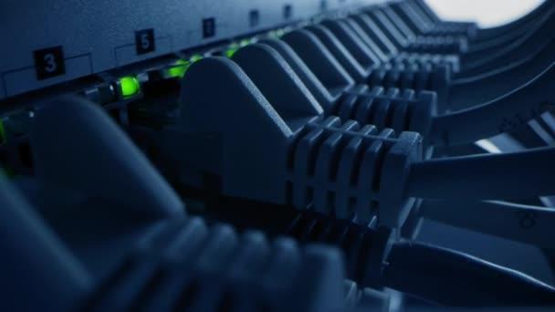 Makroaufnahme: Ethernet-Kabel, die mit blinkenden Lichtern an Router-Ports angeschlossen werden. Telekommunikation und Daten: RJ45-Internetanschlüsse an Modem-LAN-Switches. Seitenansicht Kippbare bewegliche Kamera