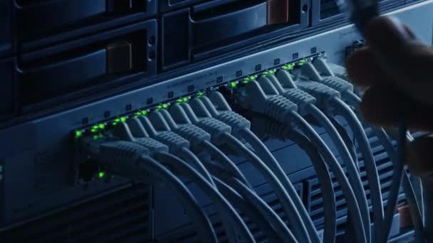 Makroaufnahme: Person steckt RJ45 Internet Connector in LAN Router Switch. Informationskommunikationsnetzwerk mit Datenkabeln, die mit blinkenden Lichtern mit Modem-Ports verbunden sind