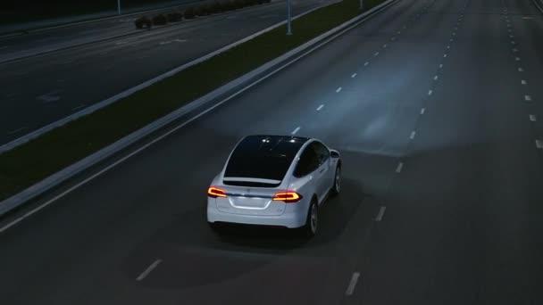 Letecký Drone Follow Shot of a Modern Luxury White Electric SUV Driving on Urban Highway. Baterie poháněné auto pohybující se prázdnou cestou s reflektory v noci. Futuristická Autonomní Autojízda.