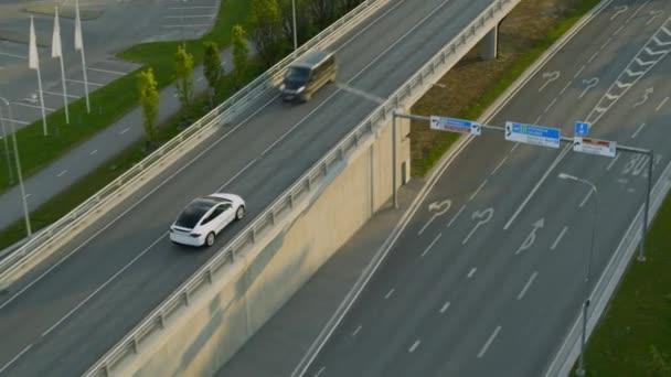 Letecký Drone Pohled na moderní luxusní White Electric Crossover Jízda na městské silnici během slunečného dne. Baterie poháněné auto jede přes most na dálnici. Futuristická Autonomní Autonomní řízení SUV.