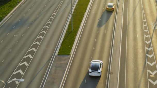 Aerial Drone View of a Modern White Electric SUV Driving on Urban Road During Day Time. Battery Powered Car Changes Lane and Passes a Golden Luxury Sedan. Futuristic Crossover with Panoramic Roof.