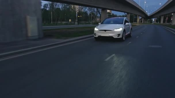 Paralelní záběry moderního luxusního bílého elektrického SUV jedoucího po městské dálnici za úsvitu. Baterie poháněné auto pohybující se Prázdnou City Road. Futuristické vozidlo s xenonovými světlomety.